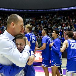 Dixie's head coach Tyler Roberts hugs his son Jordan Roberts after the team wins the 4A boys championship title at the Dee Events Center in Ogden on Saturday, Feb. 29, 2020.