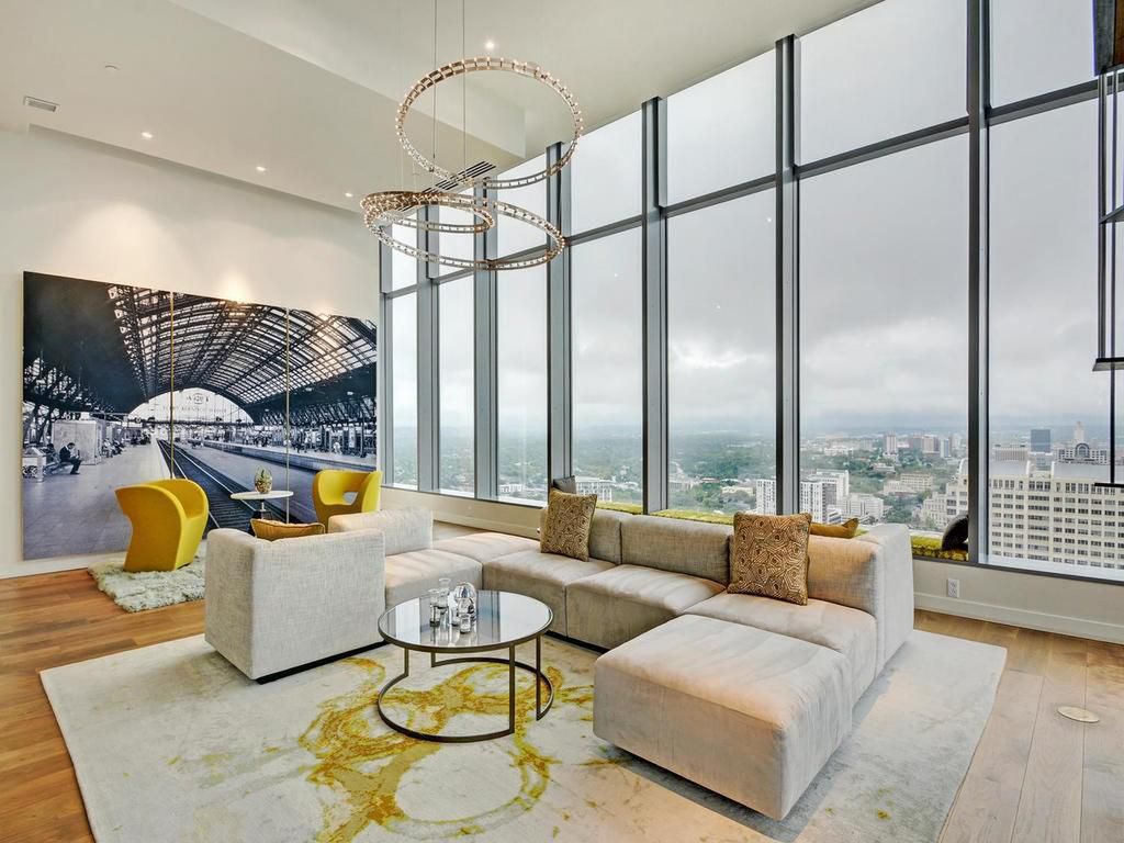 Contemporary penthouse living room with big windows, views, yellow accents