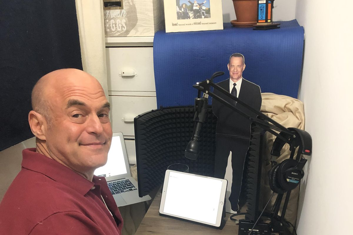 Peter Sagal sits at a nightstand with a microphone, an iPad and a Tom Hanks cutout on top.