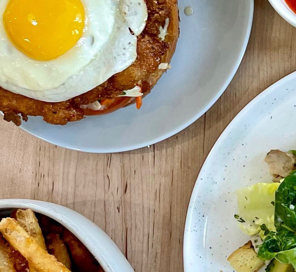 A sunny side up egg with chicken, hot honey, on a brioche bun