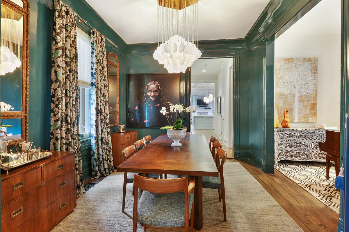 A formal dining room with glossy hunter green walls and a modern chandelier