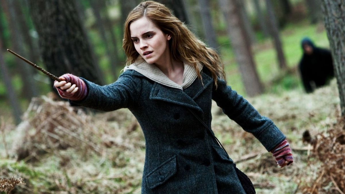 Hermione Granger, played by Emma Watson, holds up her wand for a fight in the woods.