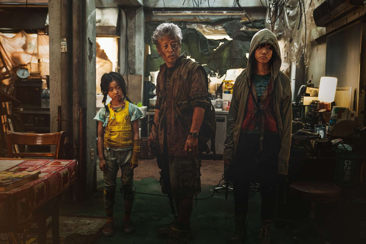 a young girl, old man, and teen stand in a ramshackle home in Train to Busan Presents Peninsula