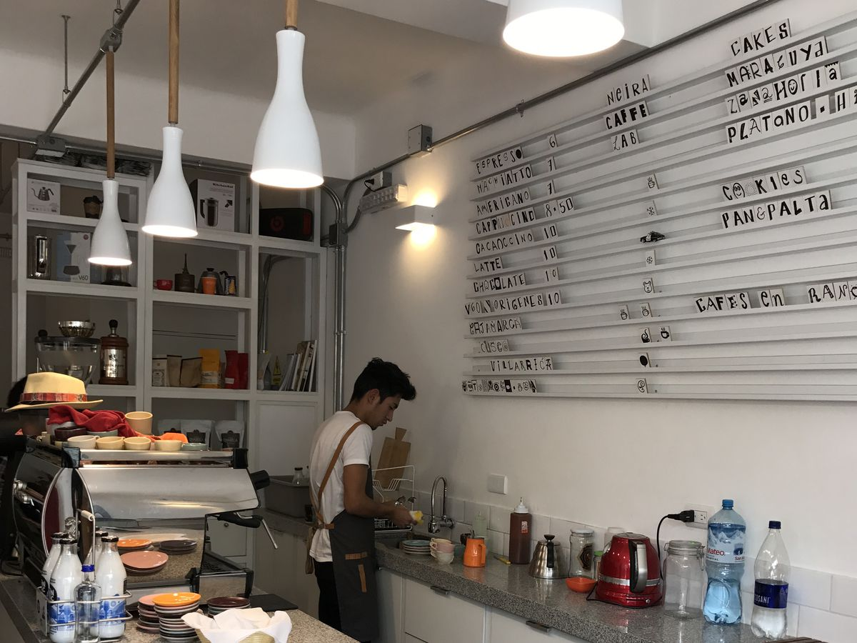A marble counter with jars of preserves and bags of coffee displayed in the foreground, an espresso maker at the far end of the bar, a barista preparing food behind the bar, and customizable letter board listing menu items on the back wall.