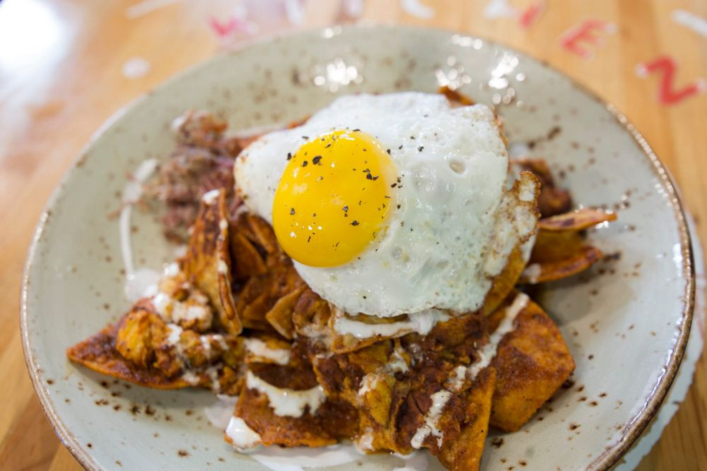 A chilaquiles dish with an over-easy egg on top