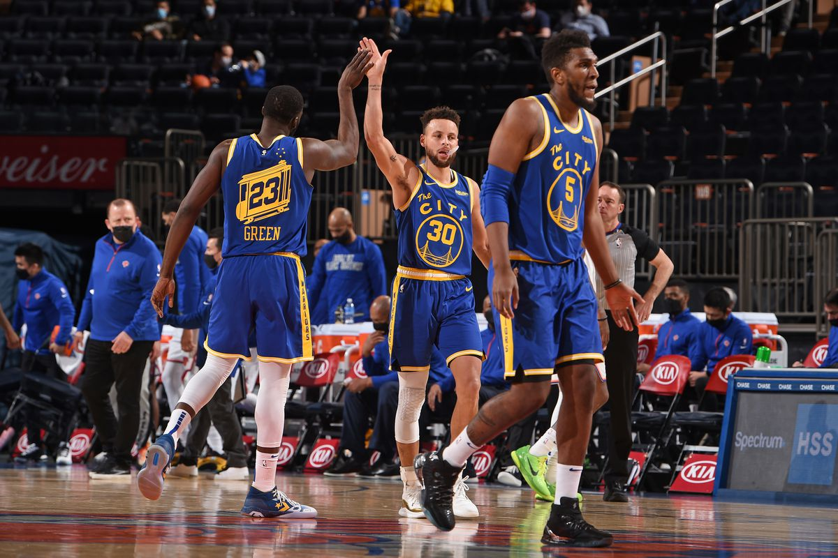 Draymond Green #23 of the Golden State Warriors and Stephen Curry #30 of the Golden State Warriors high-five during a game against the New York Knicks on February 23, 2021 at Madison Square Garden in New York City, New York.