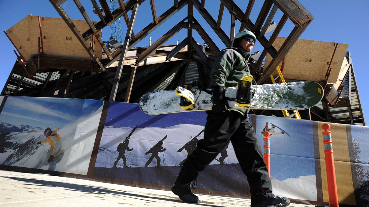 A snowboarder holding his board walks past a construction site.