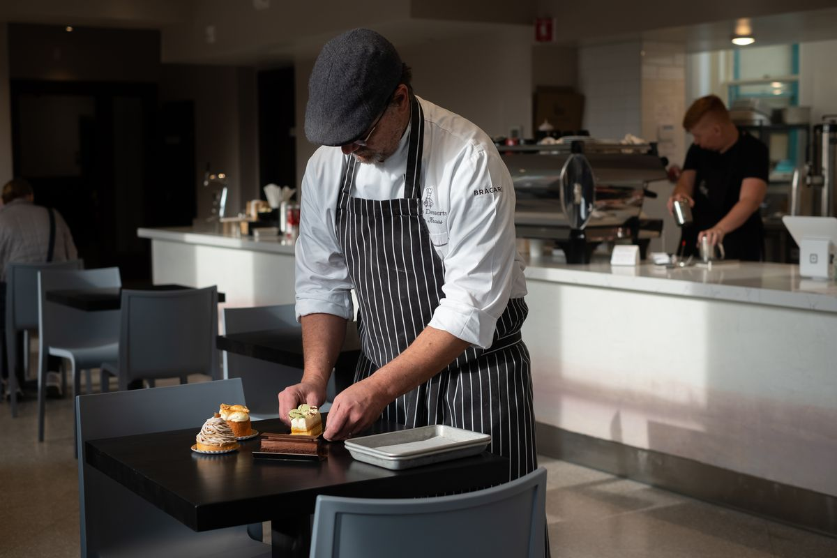 John Kraus is caught in a beam of light inside Rose Street Patisserie on West 7th, carefully placing desserts on plates