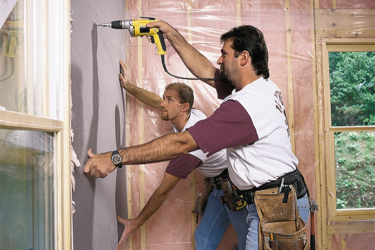 Two Men Drilling In Drywall