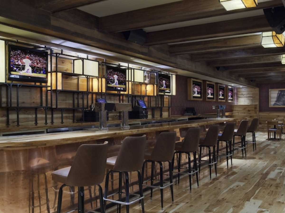 A bar space has a polished light wood floor and bar lined with eight brown backed bar stools. Three televisions sit behind the bar, situated inside a geometric shelving and lighting unit.