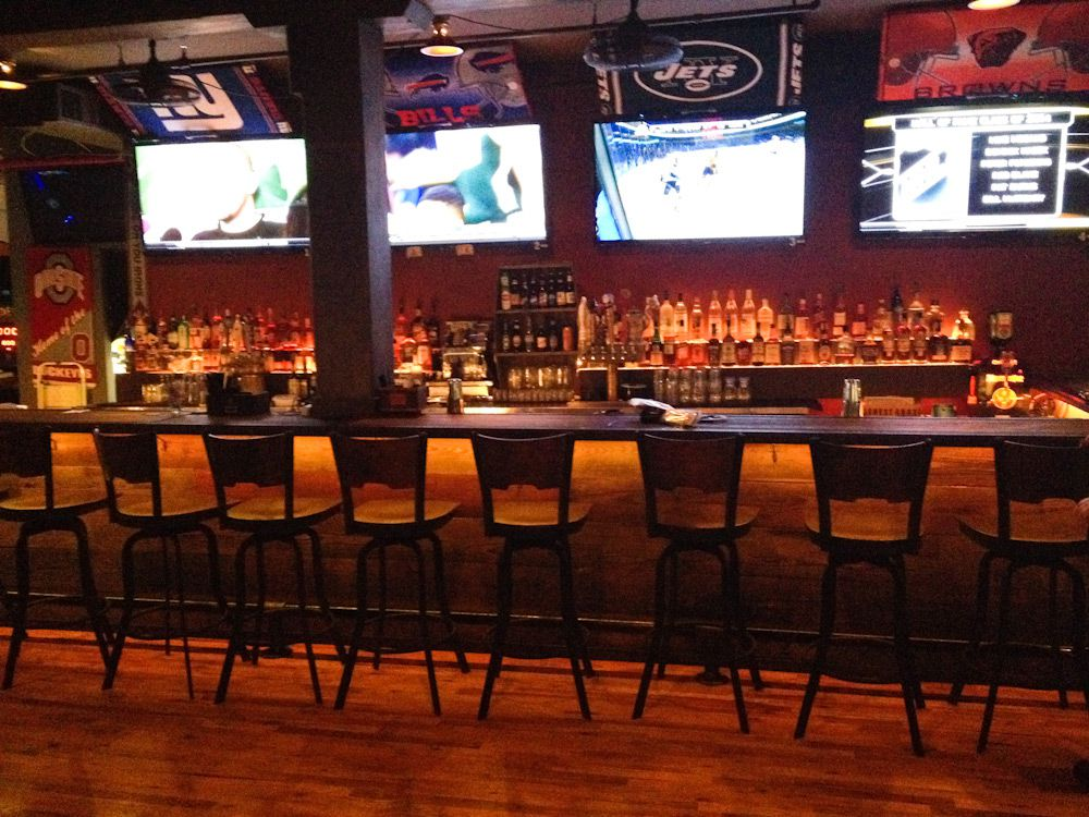 A bar lined with chairs looking up at TVs