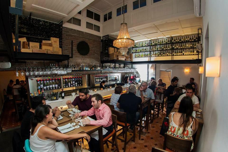 Customers sit at tables inside a cozy bar, with pendant lights, rows of bottles along the bar and high on a back wall, and dark tiled flooring