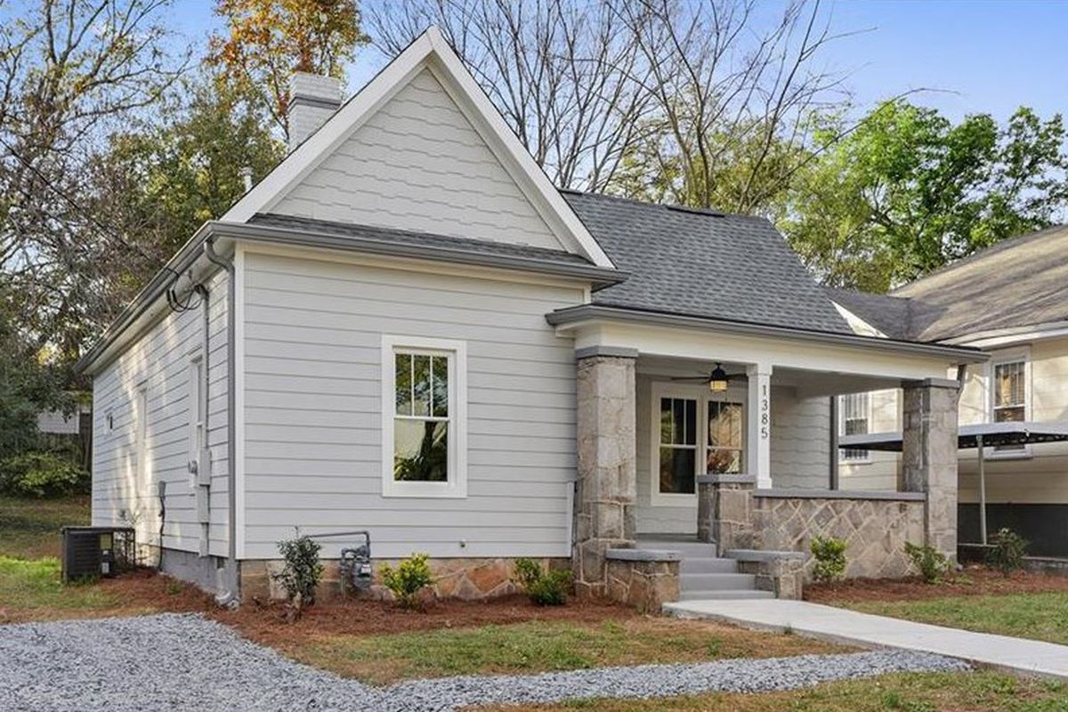 Gray house with front porch and gravel driveway.