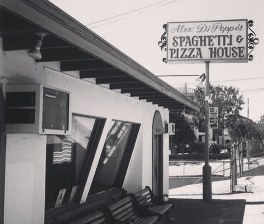 A black and white photo of an old school Italian restaurant with signage.