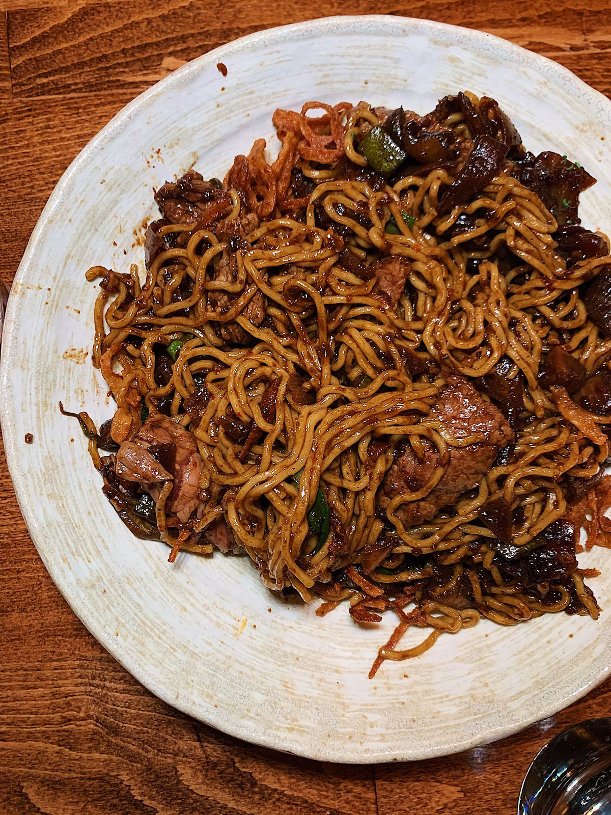 An overhead shot of a white bowl filled with brown noodles, beef, and assorted vegetables.
