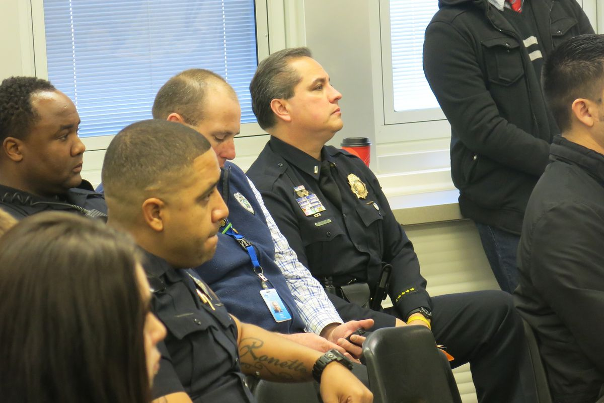 Members of the Denver Police Department watch as students from Manual High School share speeches about Ferguson.