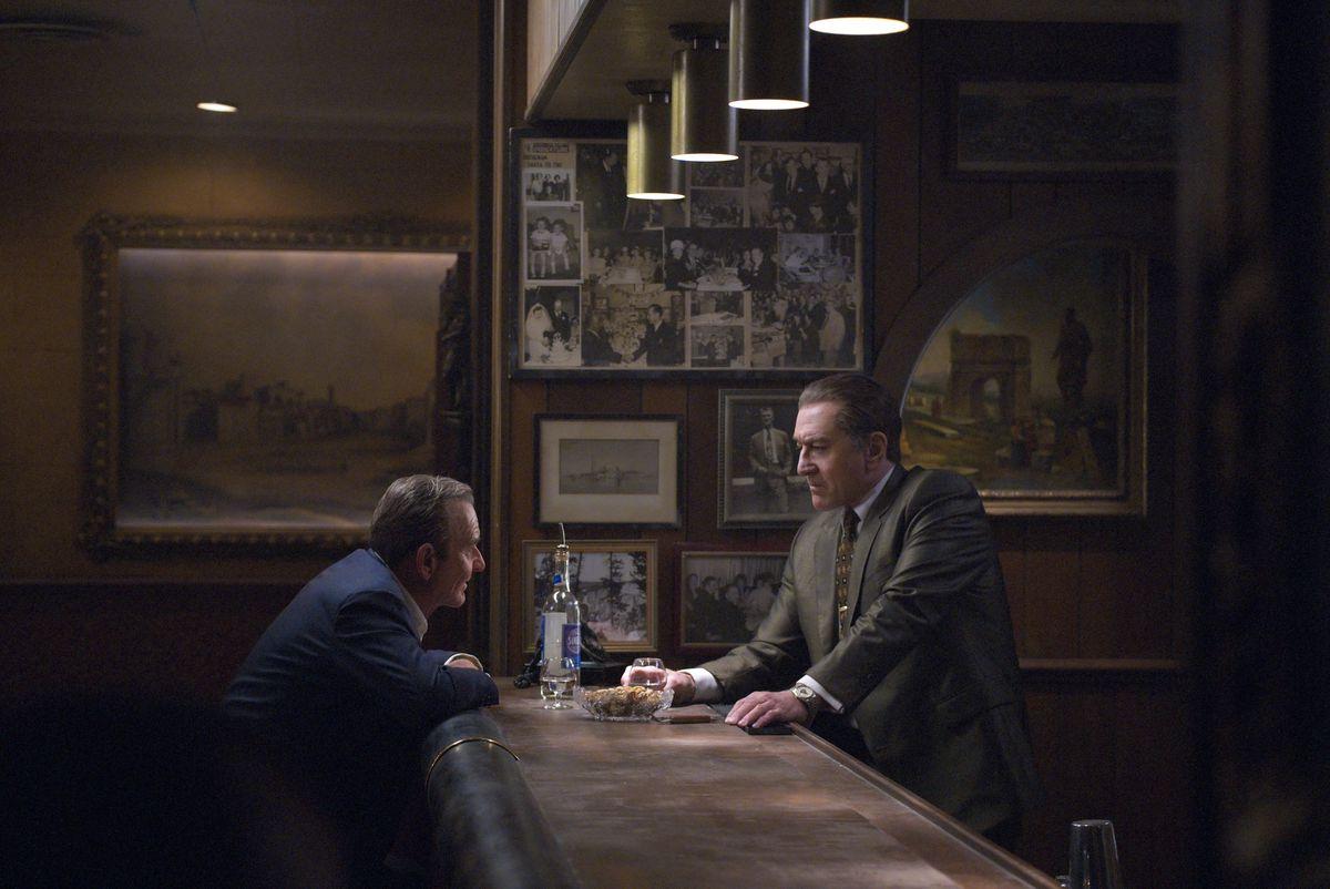 Pacino as Jimmy Hoffa and De Niro as Frank Sheeran across from each other at a bar in The Irishman