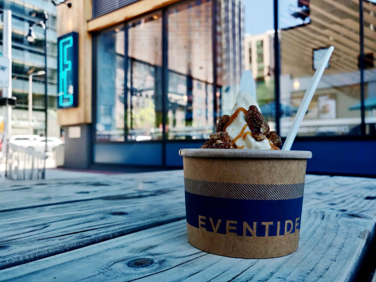A brown paper cup with a blue logo reading Eventide sits on a wooden picnic table, holding a twist of soft serve ice cream. In the background, a restaurant exterior with large windows and a blue neon letter E is visible.