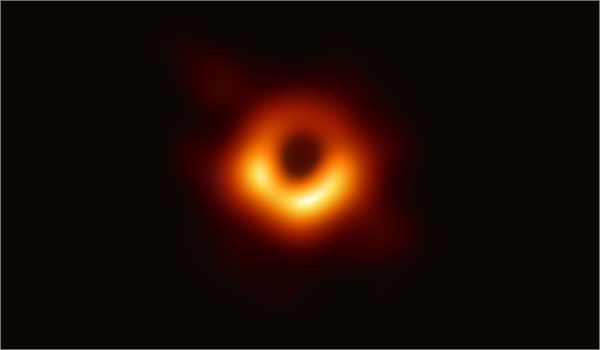 An orange ring of light surrounds a black hole.