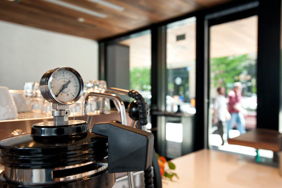 A close-up photo of coffee making equipment at Little Owl Coffee on a counter with windows and blurred people outside visible