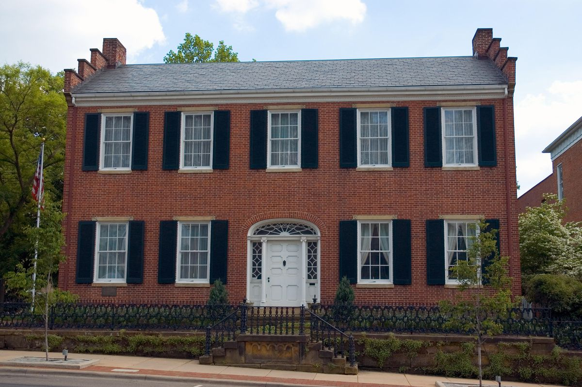 Red brick Federal style home with symmetrical design.