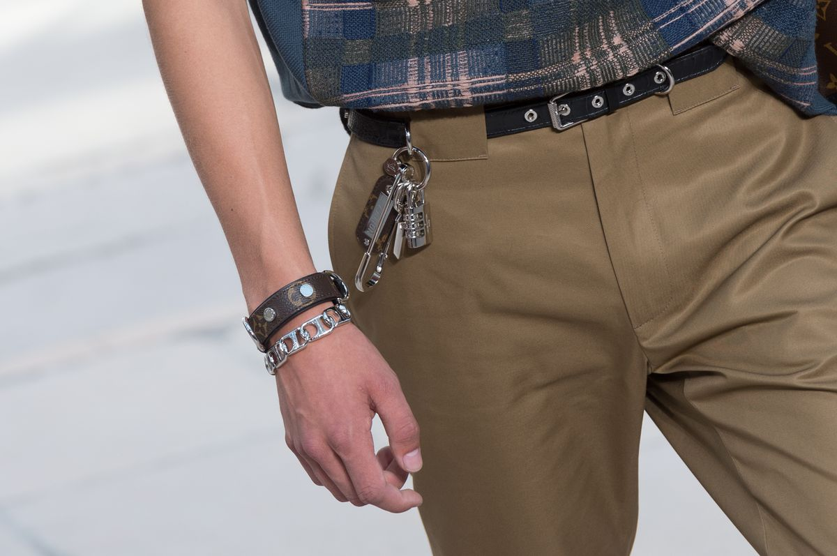 A model walks the runway wearing keys attached to his belt loop, along with a leather cuff and a chain link bracelet.
