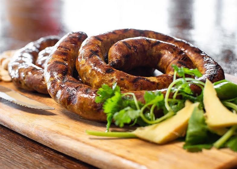 Rolls of sausage on a cutting board with cheese and herbs