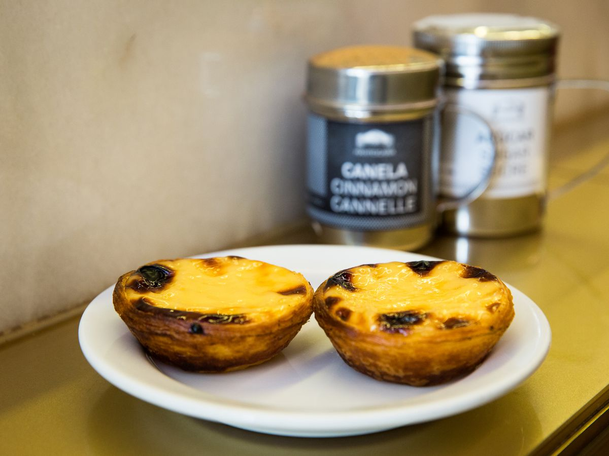 Two tarts on a plate on a wooden counter beside condiment shakers