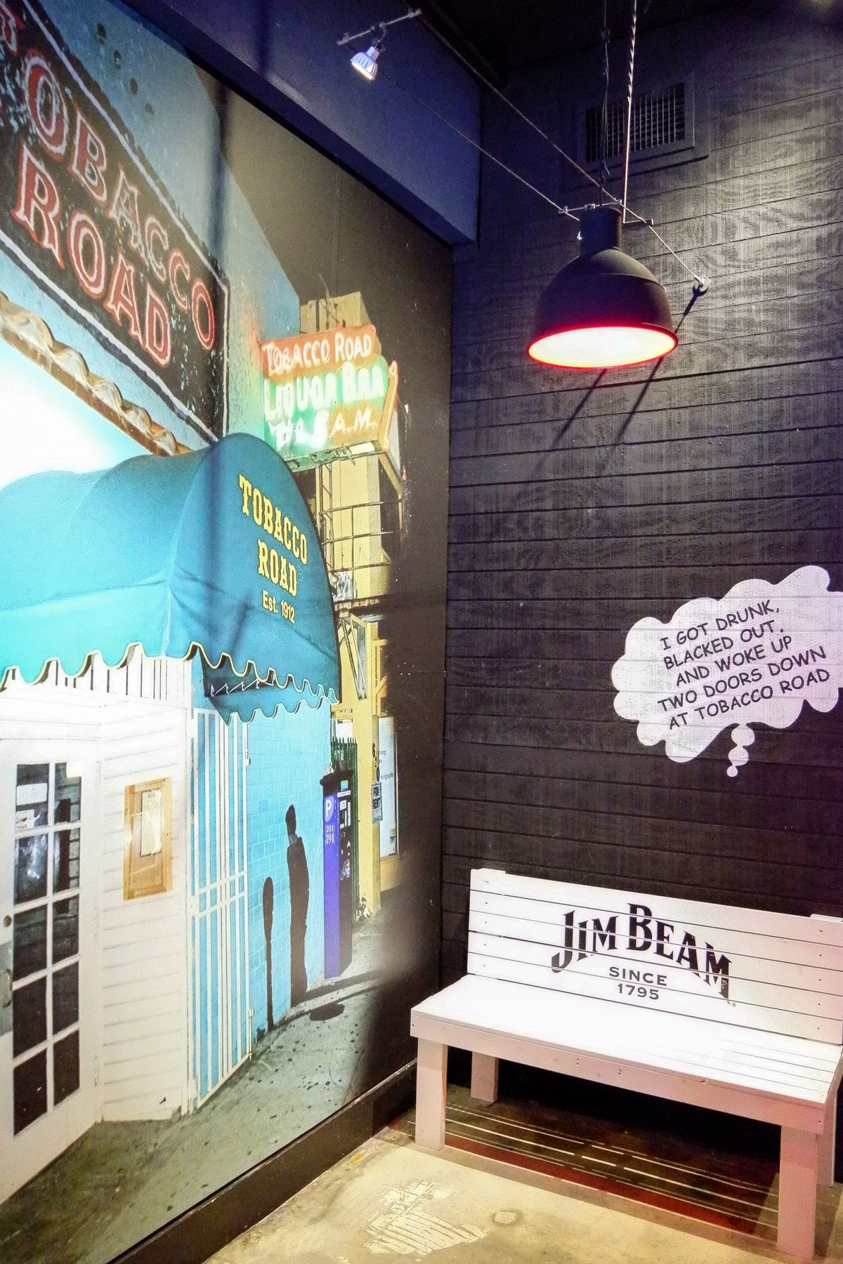 White bench against black wall, next to another wall that has a drawing of an old school bar