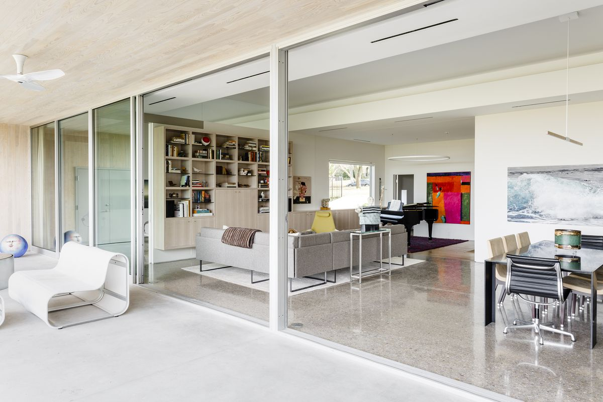 The living room-dining room is connected to the patio by floor to ceiling glass sliding doors.