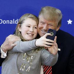Republican presidential candidate Donald Trump poses for a selfie with a young attendee during a campaign stop on Saturday, Jan. 16, 2016, in Portsmouth, N.H.