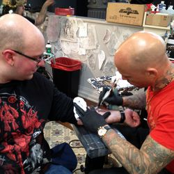Ami James works on the first tattoo of the morning.