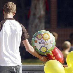 An American Fork High student touches a balloon left in memory of Heather Christensen.