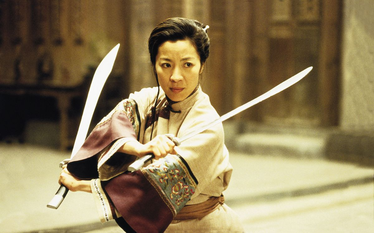 Yu Shu Lien (Yeoh) holds up two swords.