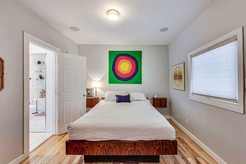 A bedroom with a white bed spread and wood base. There is a colorful circular art above the headboard and two night stands with a lamp. The bathroom door is open.