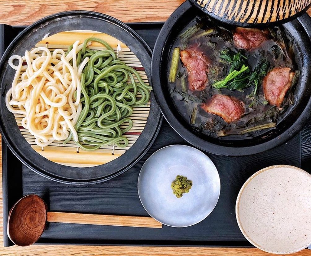 Green and white udon noodles alongside soup
