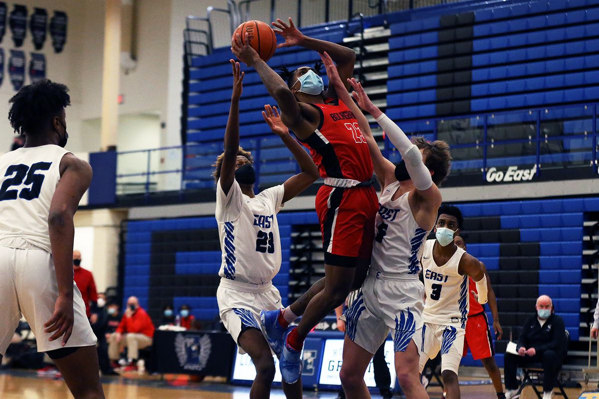 Bolingbrook's Kai Evans (23) goes up for a shot between Lincoln-Way East's Khalil Ross (23) and Ryan Sucha (5).