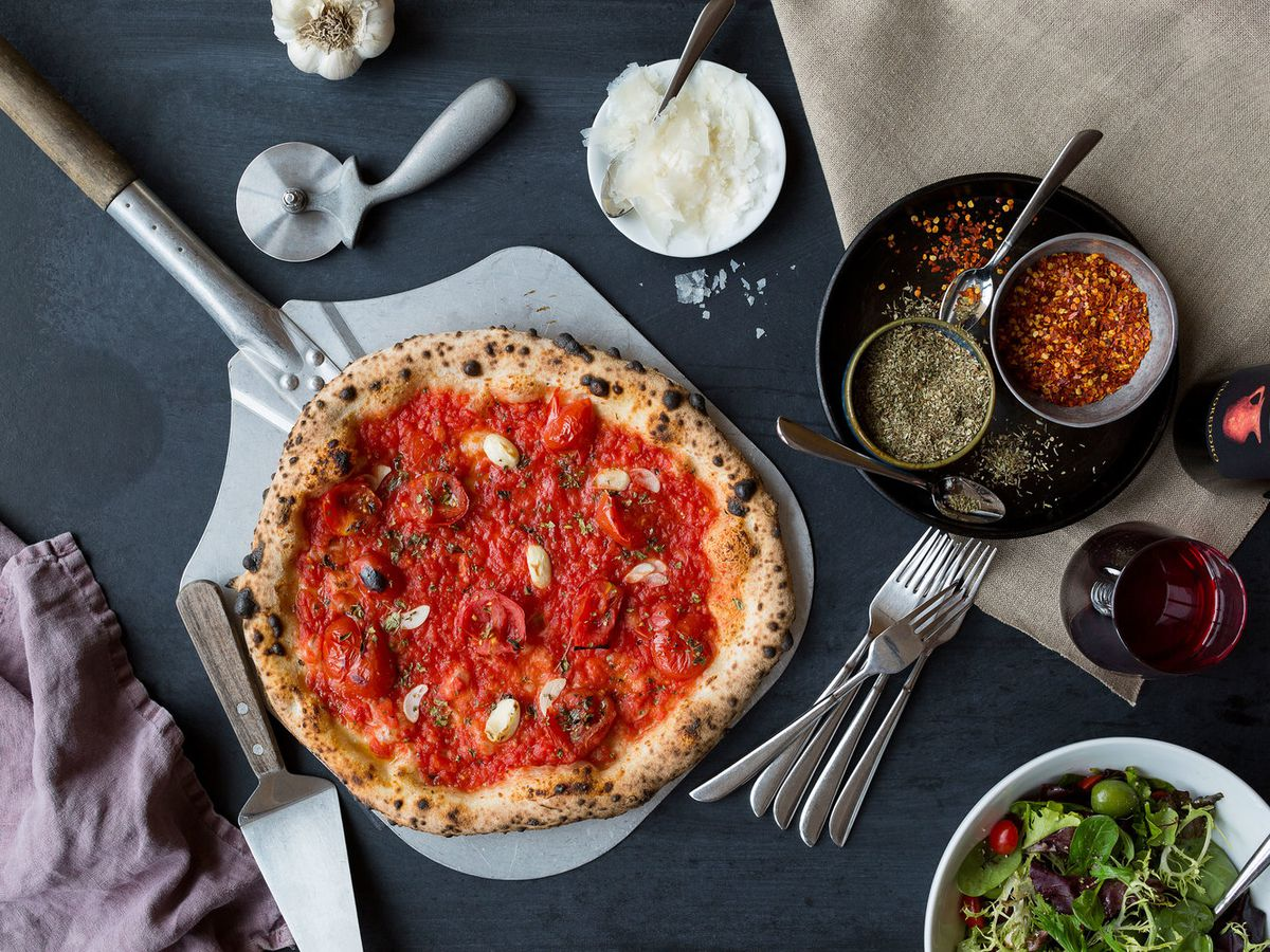 Pizza, salad, wine, and other ingredients spread out on a counter.