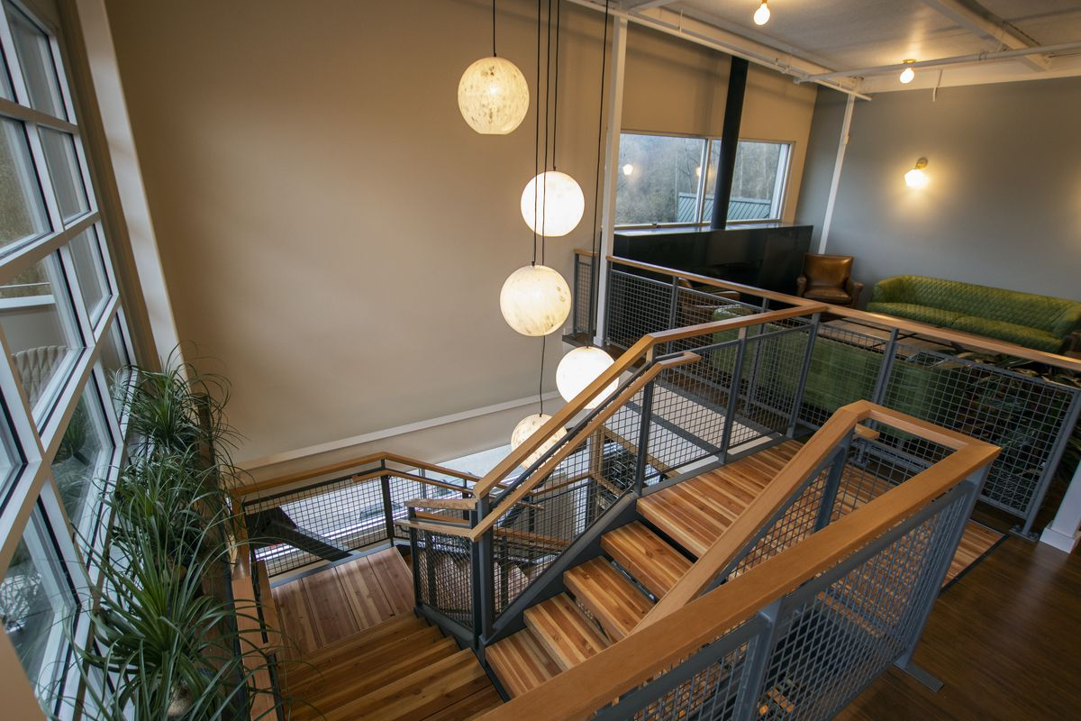 A view of a wooden stairwell near a lounge, with globe-shaped lights and a window on the left.