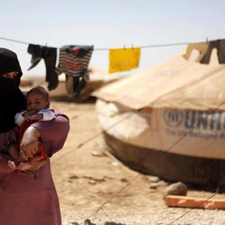 Syrian refugee, Omm Ahmed, from Daraa, Syria, carries her newly-born infant near her tent, at Zaatari Refugee Camp, in Mafraq, Jordan, Sunday, Sept. 2, 2012.