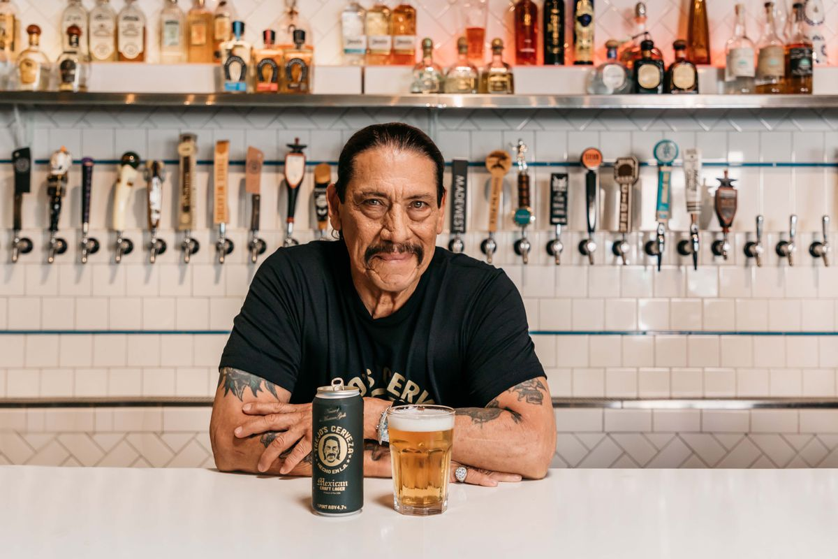 A burly man behind a bar smiling with a can of beer and glass of beer on the bar.
