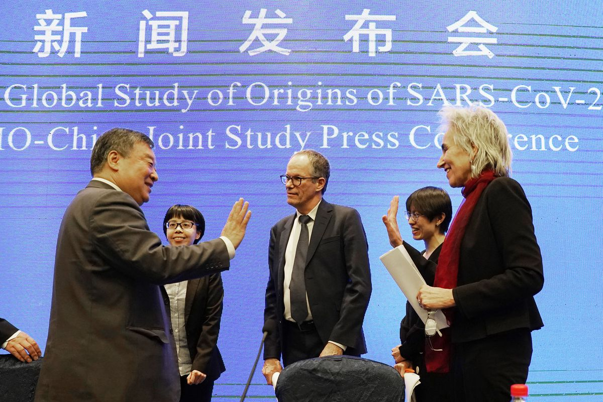 Marion Koopmans, right, and Peter Ben Embarek, center, of the World Health Organization team say farewell to their Chinese counterpart Liang Wannian, left, after a WHO-China Joint Study Press Conference held at the end of the WHO mission in Wuhan, China, Tuesday, Feb. 9, 2021.