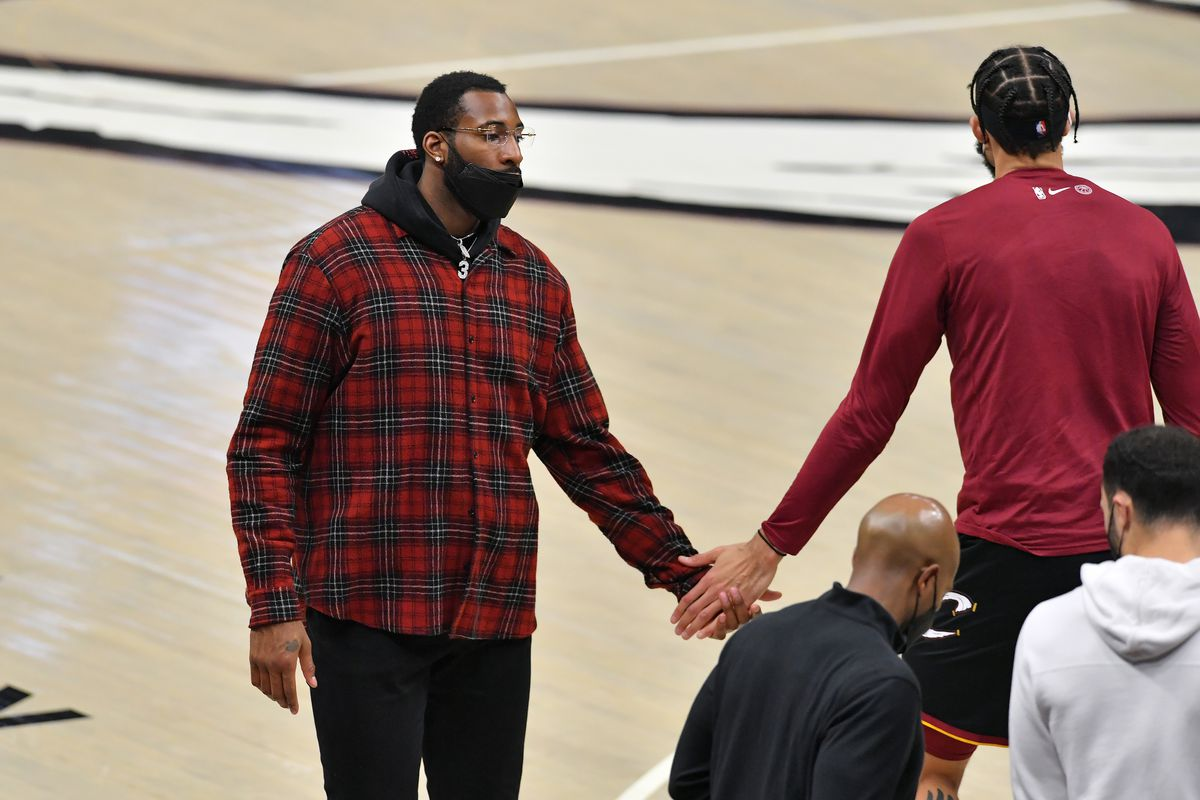 Andre Drummond celebrates with JaVale McGee of the Cleveland Cavaliers during a timeout during the second quarter against the Denver Nuggets at Rocket Mortgage Fieldhouse on February 19, 2021 in Cleveland, Ohio.