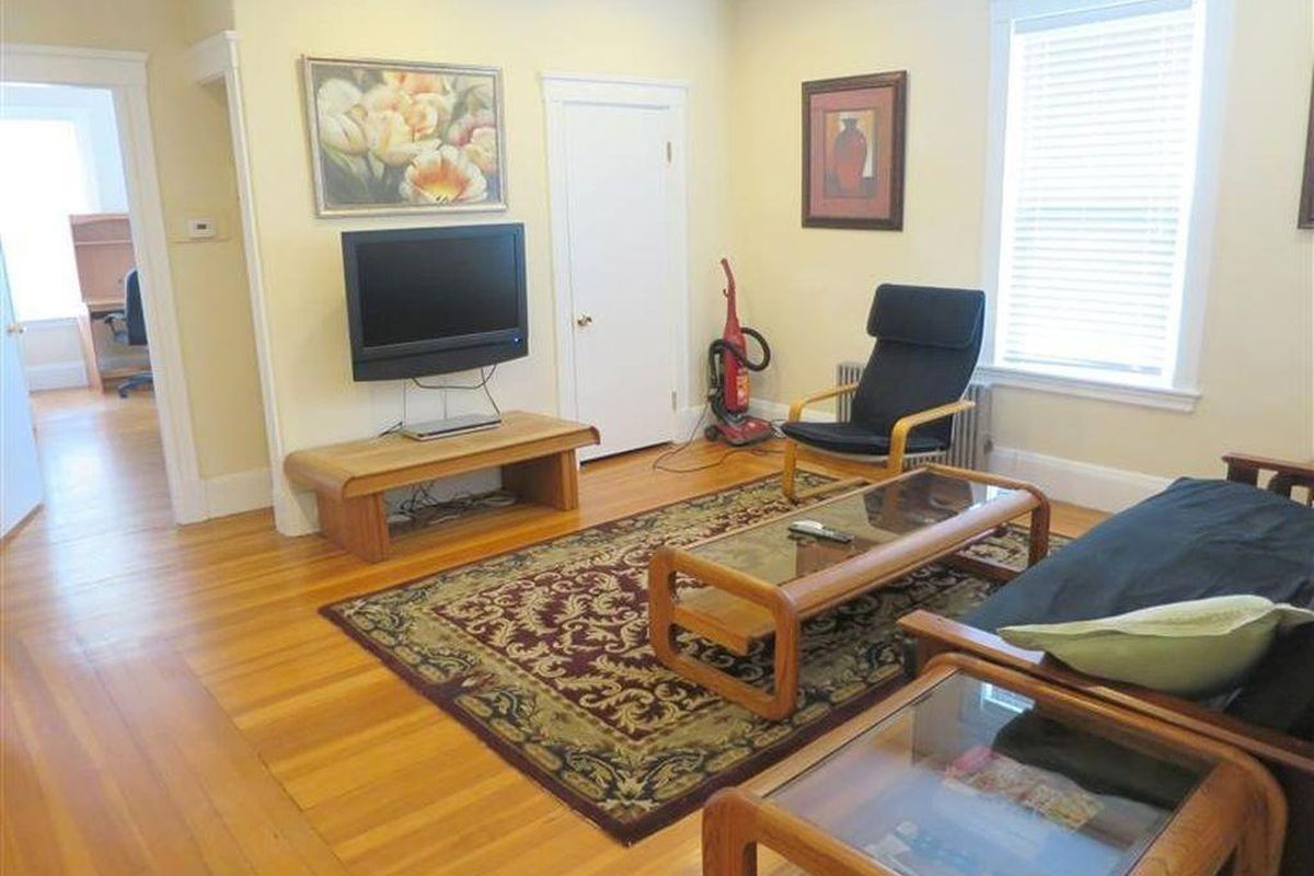 A small living room with furniture facing a TV.