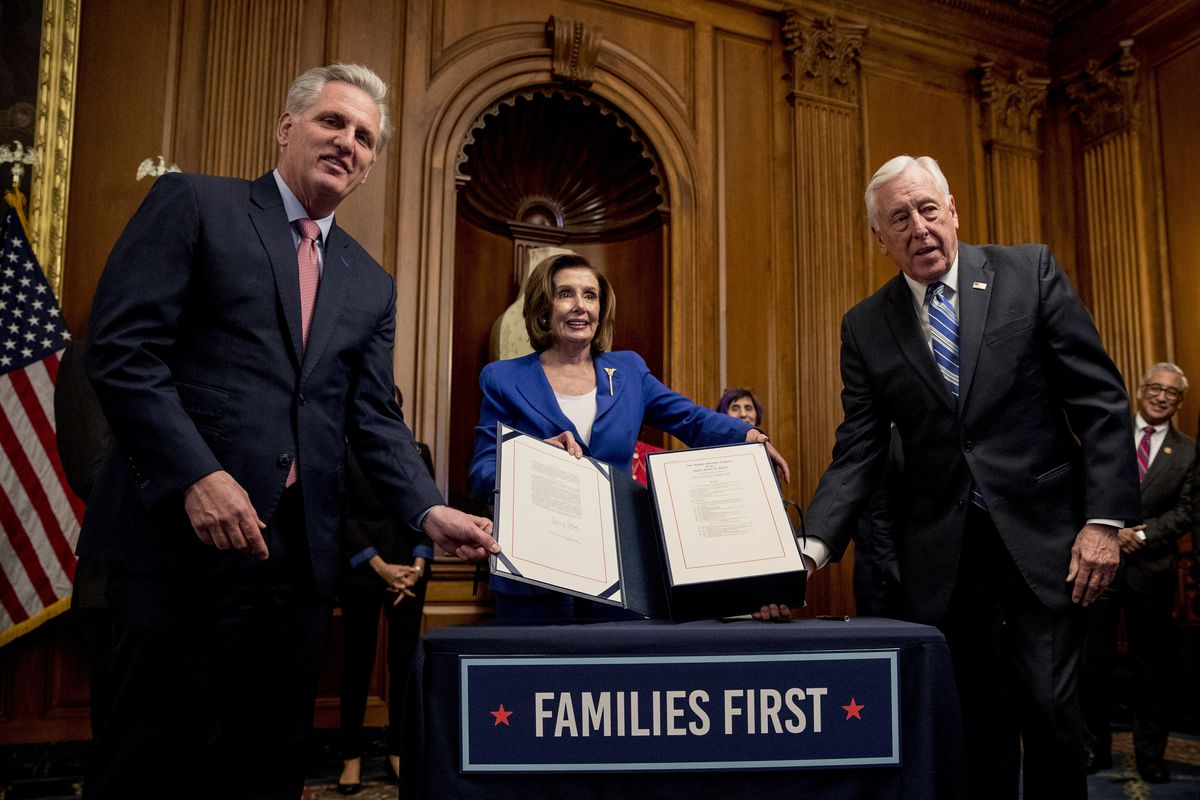 House Speaker Nancy Pelosi celebrates the passage of the $2.2 trillion relief act with House Minority Leader Kevin McCarthy, Republican of California, and House Majority Leader Steny Hoyer, Democrat of Maryland, on March 27. The measure includes a $1,200 direct payment to qualifying adults.