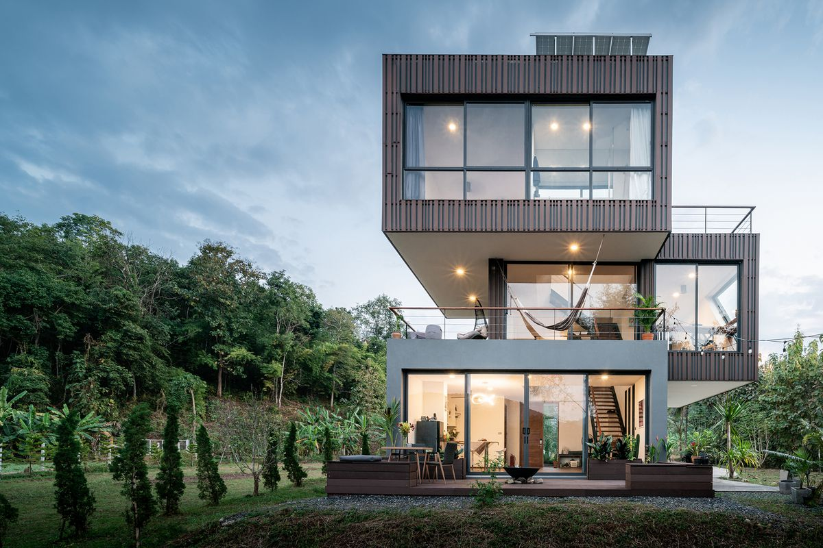 House built from three stacked boxes, surrounded by lawns and trees.