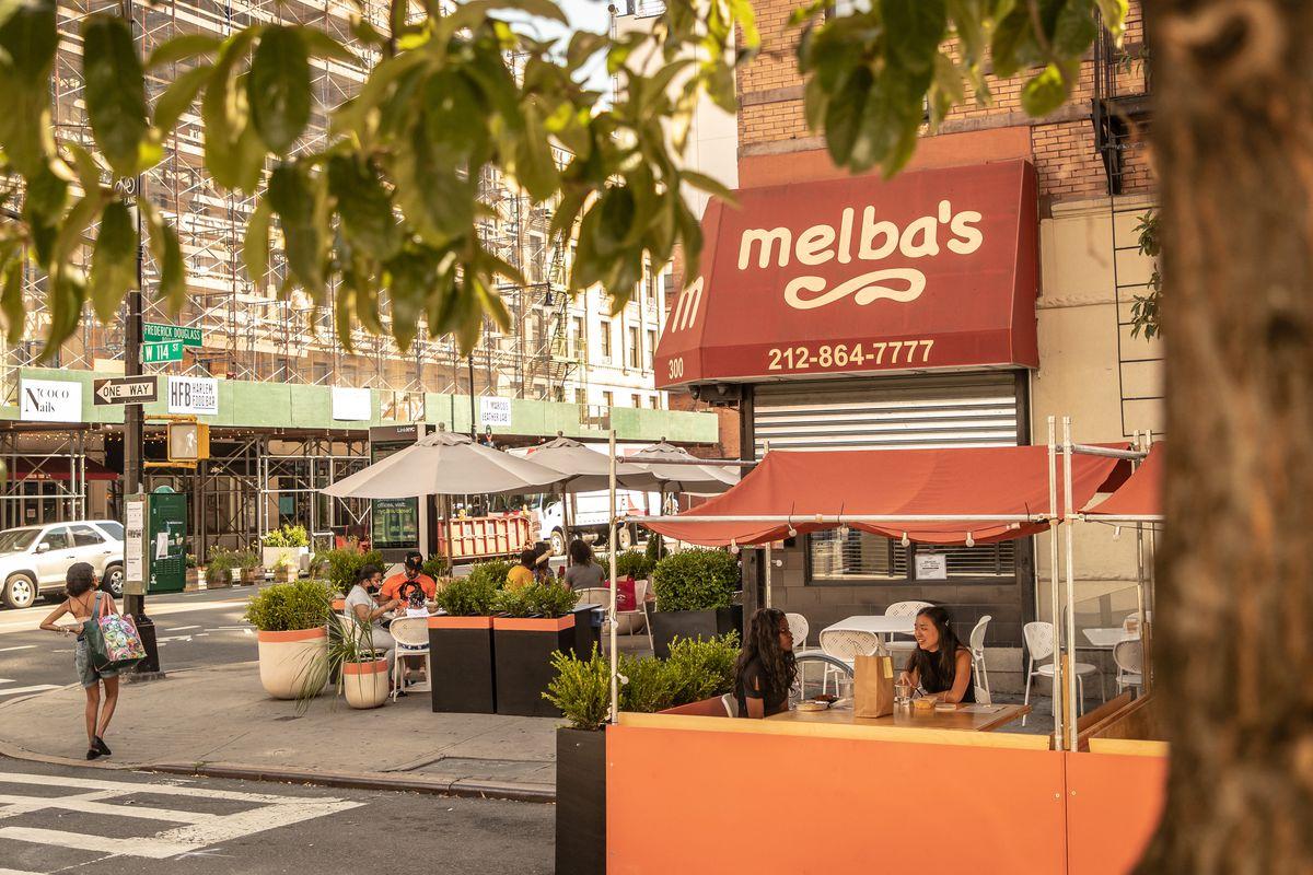 Customers dining outside Melba's, under orange awnings