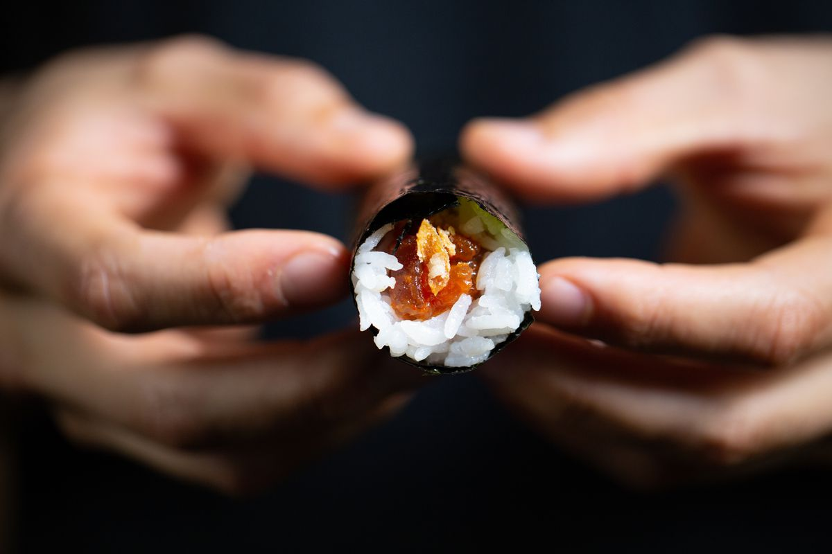A picture of someone holding a roll of sushi