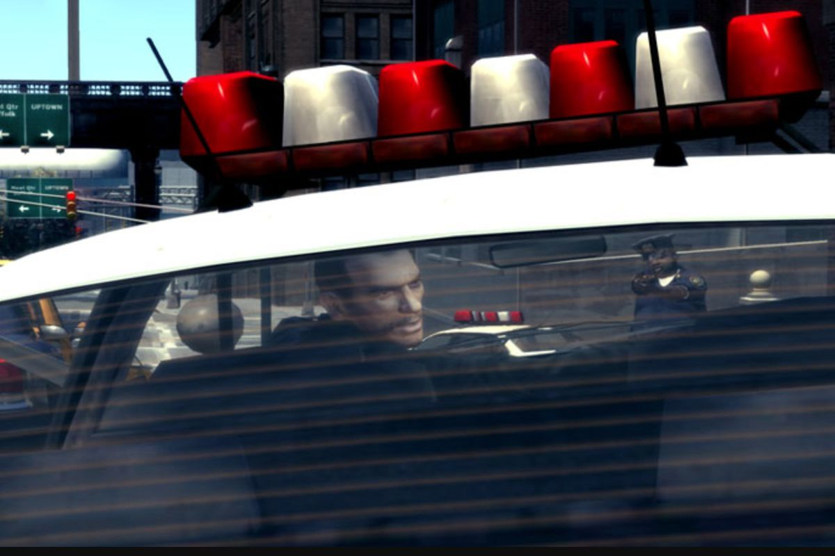Man in front of police car looking back at camera
