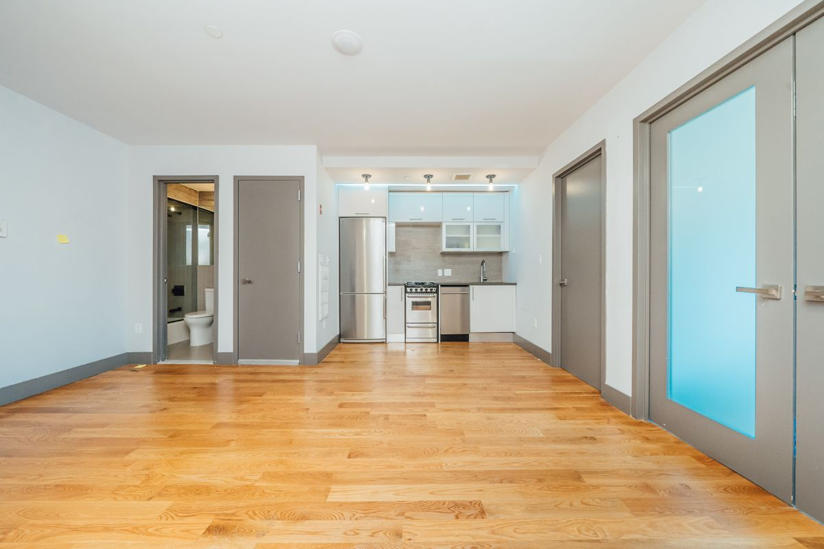 A living area with hardwood floors, white walls, several doors, and an open kitchen with white cabinetry in the back.